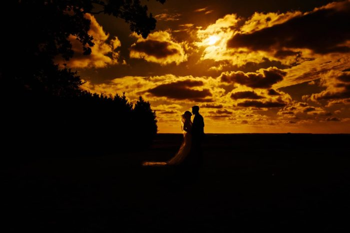 beautiful and dramatic sunset portrait of bride and groom