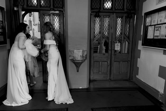bridesmaids peep into the church