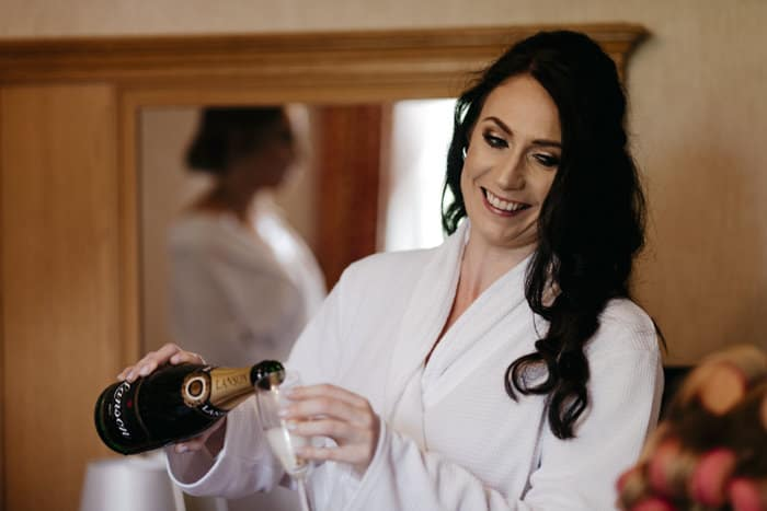 bridesmaid pours a drink