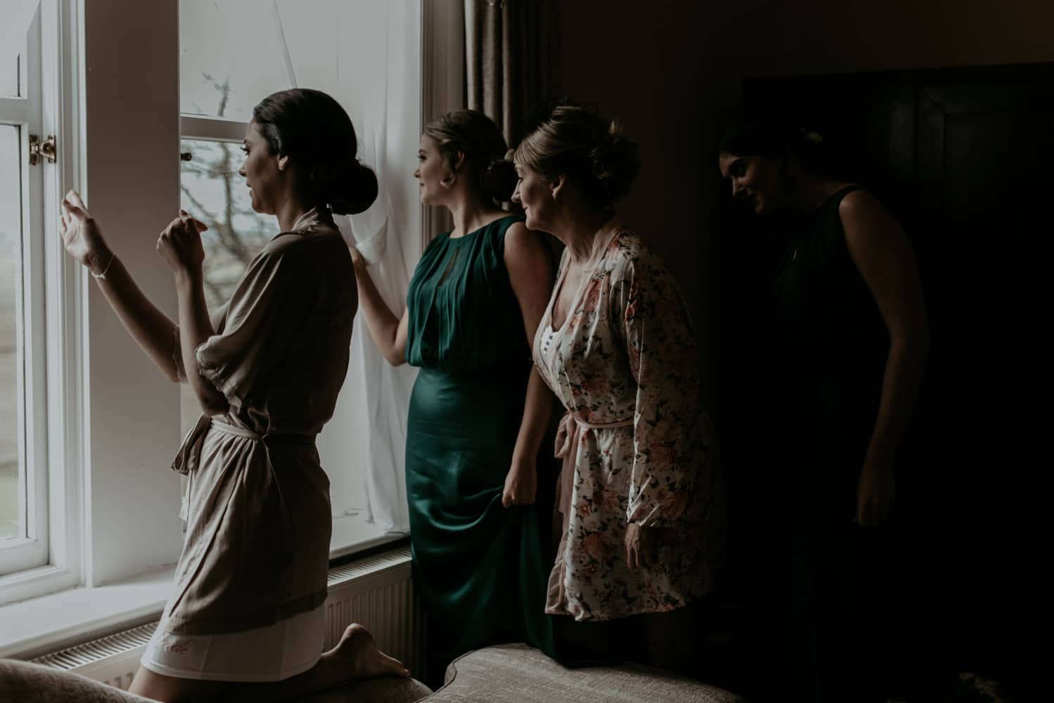 bride and bridesmaids at the window
