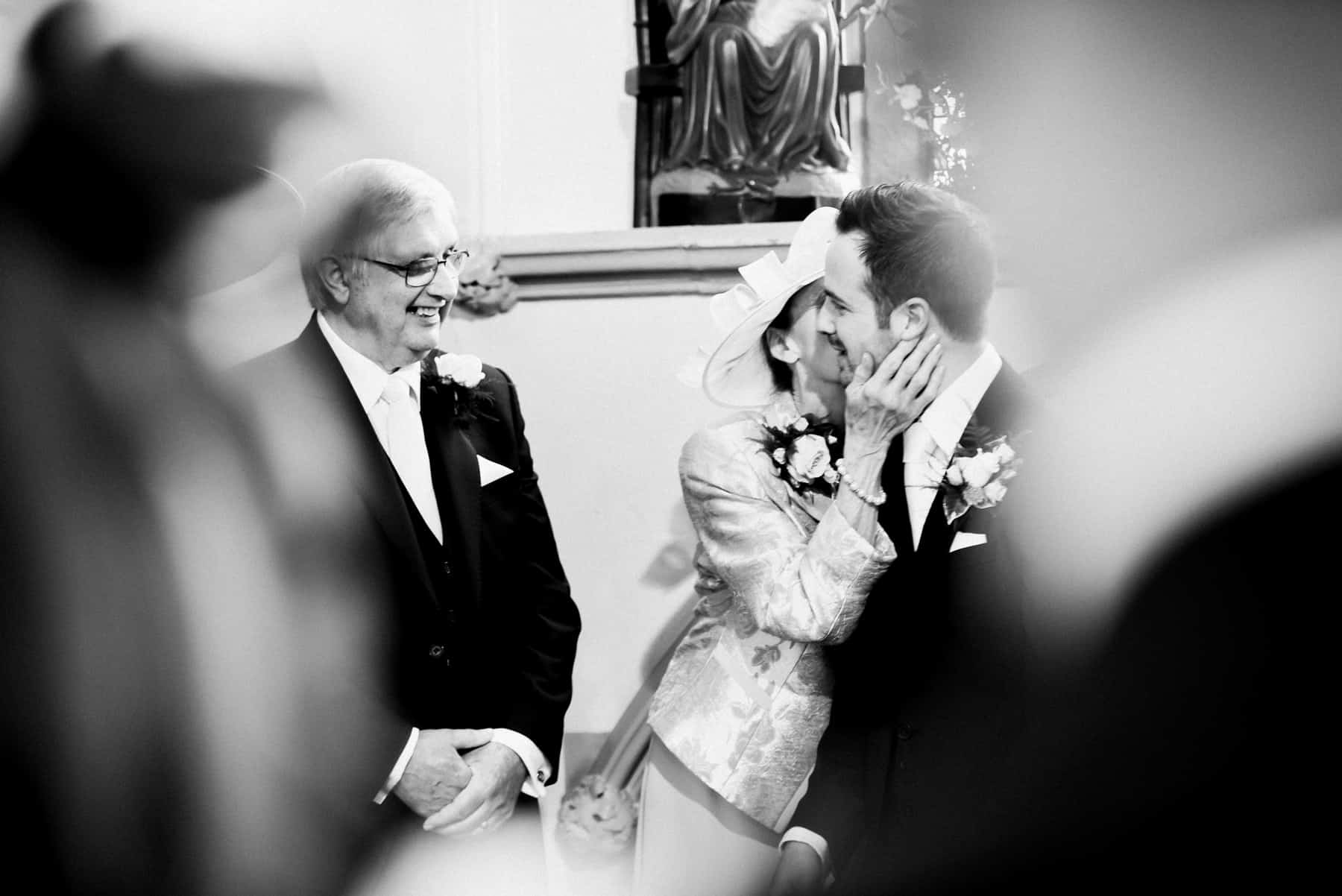 bride's mum kisses the groom