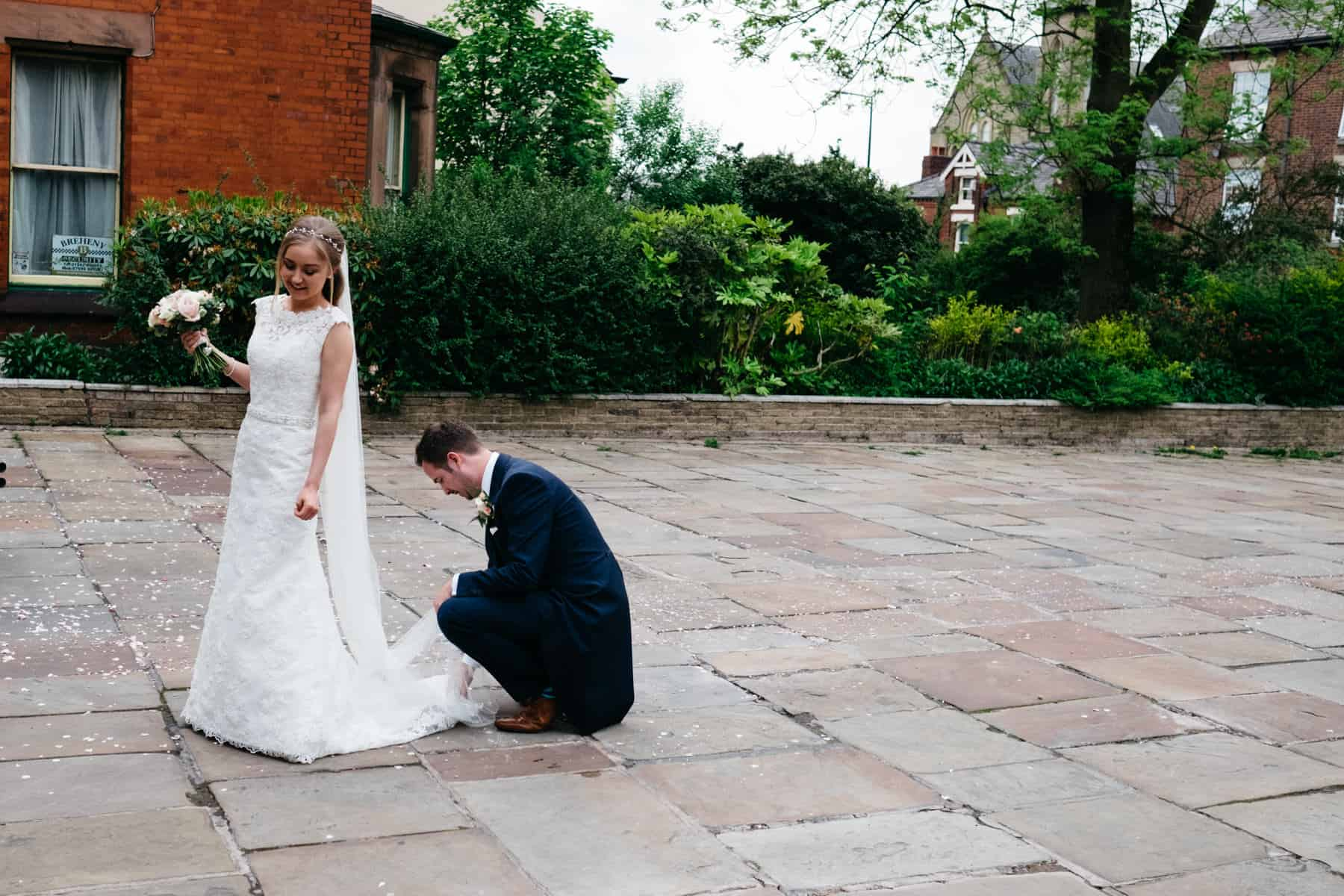 groom fixes bride's dress