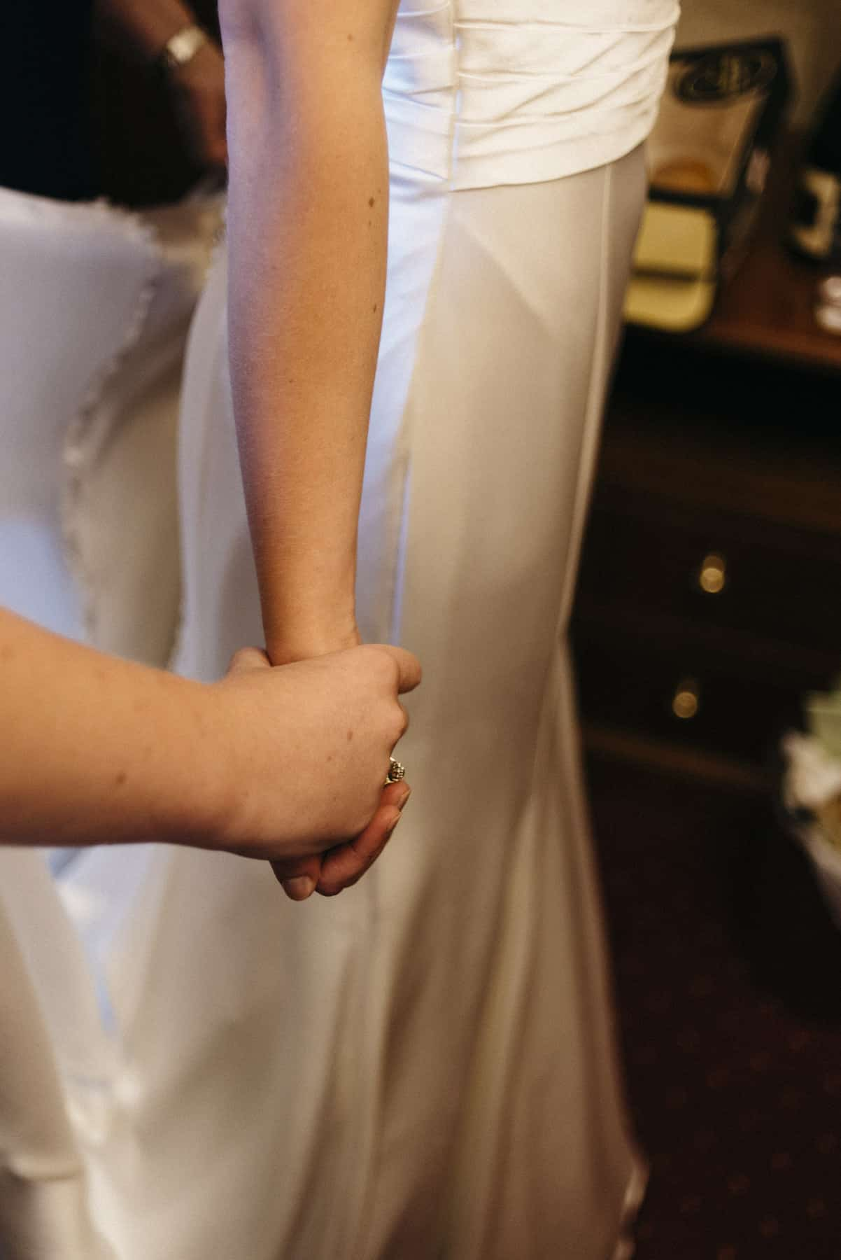 bride and her mum hold hands detail