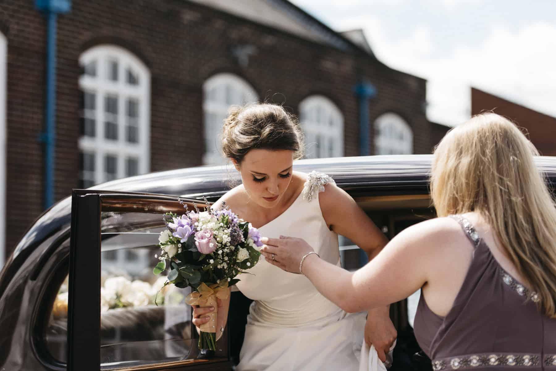 bridesmaid helps bride out of car