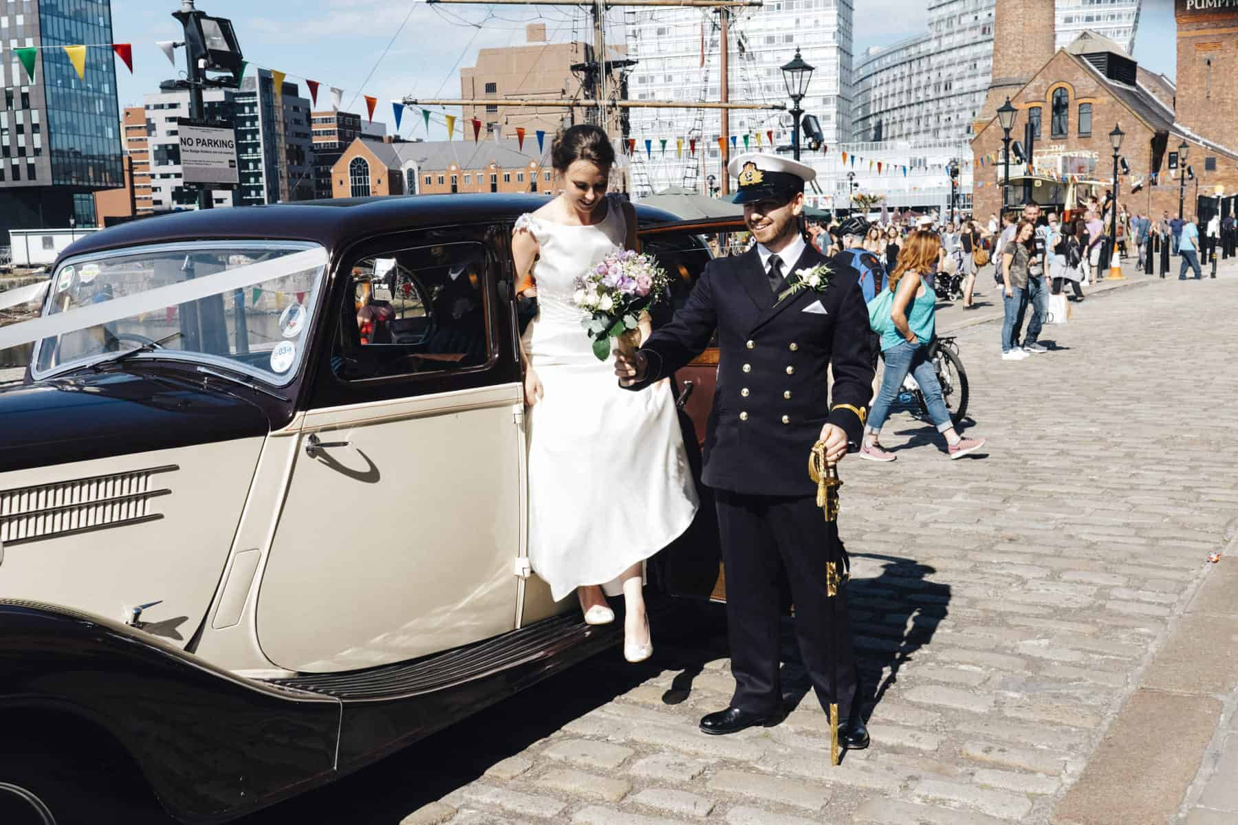 groom helps bride out of the car