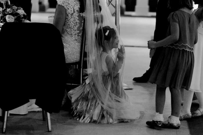 little girl hides inthe bride's veil