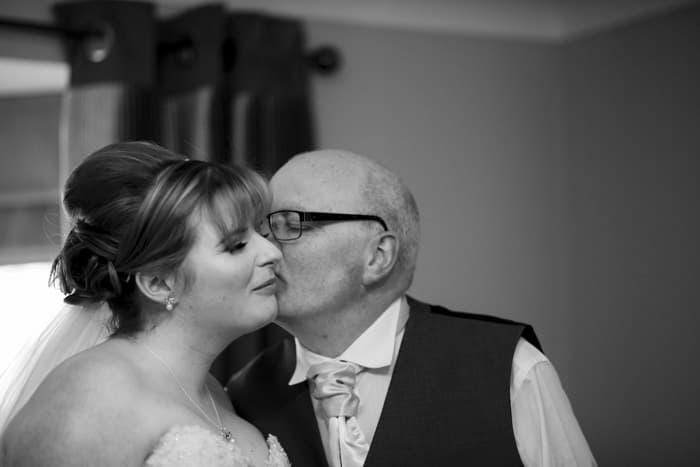bride's dad gives her a kiss