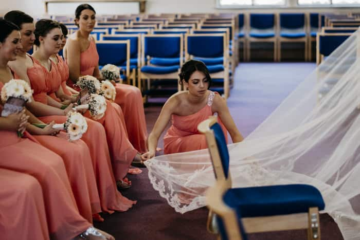 bridesmaid adjusts the dress