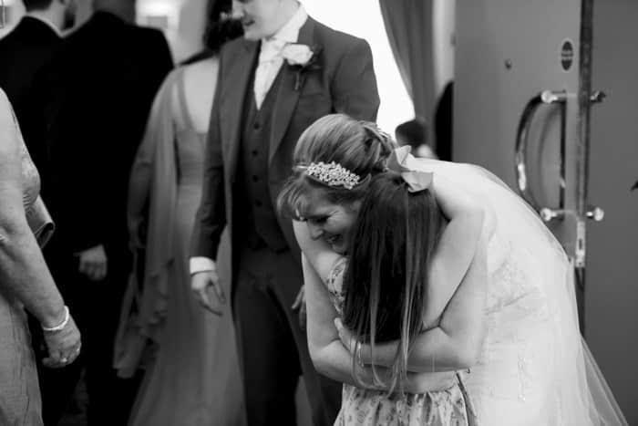 bride and young girl hug