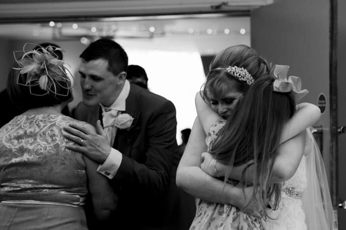 bride and groom hug guests