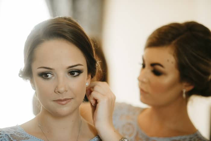 bridesmaid helps bridesmaid with earring