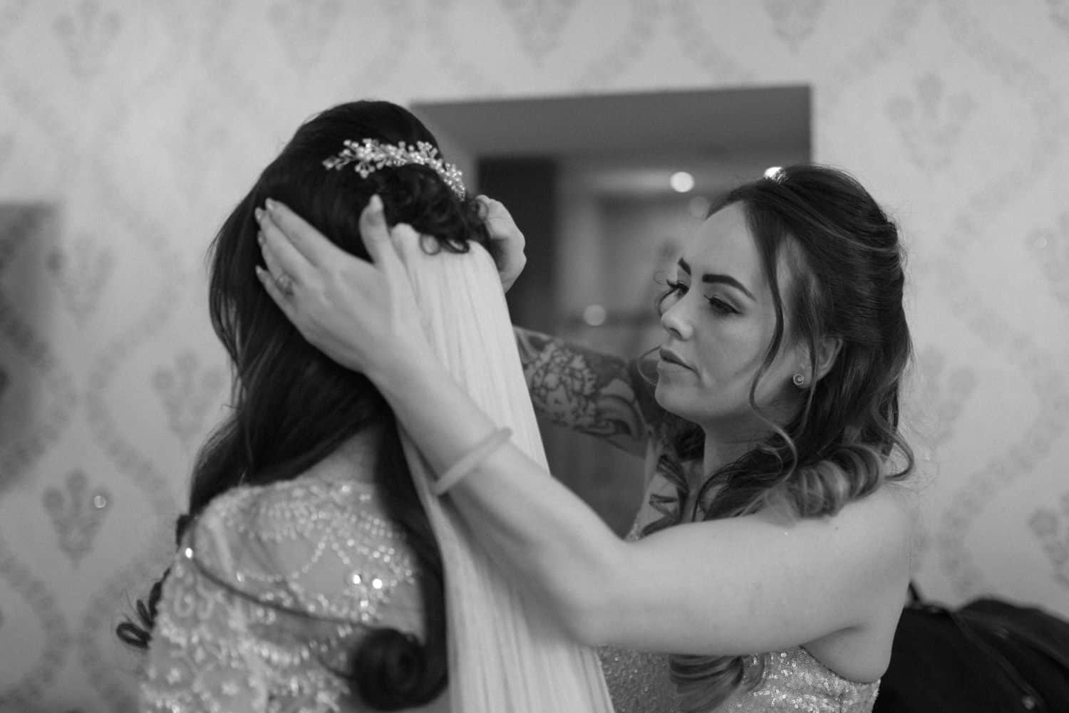 bridesmaid puts the veil on the bride